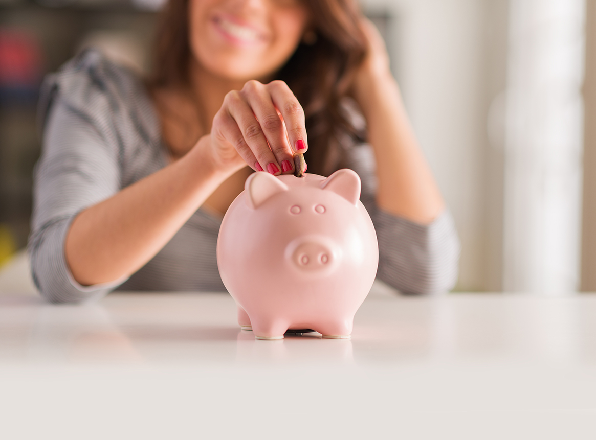 Brunette woman putting coins into a piggy bank